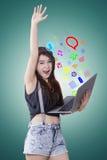 La muchacha alegre utiliza medios sociales con el ordenador portátil Foto de archivo
