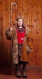 La muchacha alegre vestida en botas que llevaban de una capa y tomó al personal shepherdess Imágenes de archivo libres de regalías