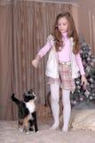 La muchacha alimenta su gato Imagen de archivo