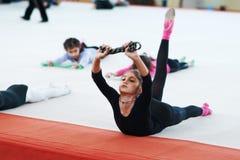 La muchacha amasa su parte posterior en la lección de la gimnasia Foto de archivo libre de regalías