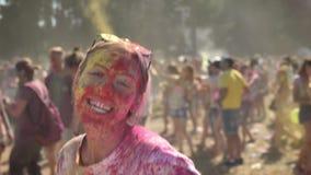 La muchacha animada joven en polvo colorido es de salto y de baile en festival del holi en d3ia en el verano, concepto del color metrajes
