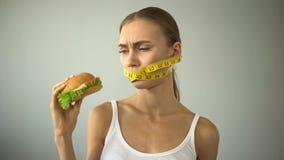 La muchacha anoréxica ata la boca con la cinta-línea, lucha con la tentación de comer la hamburguesa almacen de metraje de vídeo