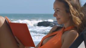 La muchacha anota pensamientos en diario contra paisaje marino