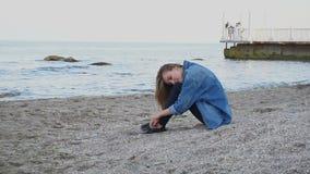 La muchacha apacible de la cámara lenta descansa sentarse en la costa y escucha la resaca en la playa arenosa caliente por la tar almacen de video