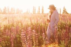 La muchacha apacible en vestido elegante del verano con el sombrero de paja hermoso que camina en campo de flor del lupine adentr Imagen de archivo