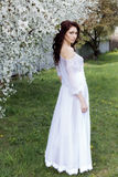 La muchacha apacible linda atractiva hermosa camina en un vestido blanco ligero en un jardín floreciente del día de verano brilla Imagen de archivo libre de regalías