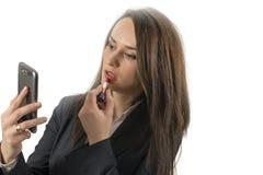 La muchacha aplica el lápiz labial que mira el teléfono como según lo en un espejo aislado Imagenes de archivo
