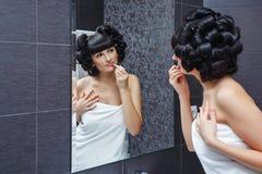 La muchacha aplica el lápiz labial en cuarto de baño Foto de archivo
