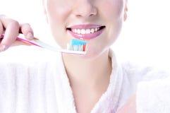 La muchacha aplica sus dientes con brocha Fotos de archivo libres de regalías