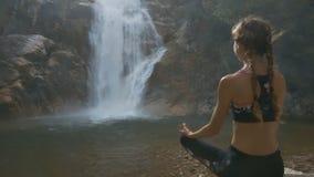 La muchacha apoyada desnuda se relaja en actitud de la yoga por la cascada