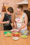 La muchacha aprende hacer una cena. Fotografía de archivo