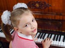 La muchacha aprende jugar un piano Fotografía de archivo libre de regalías
