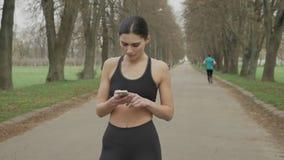 La muchacha apta de los jóvenes está mirando su smartphone, corriendo en parque en verano, concepto de la comunicación, concepto  almacen de metraje de vídeo