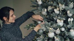 La muchacha apuesta sonriente está adornando el árbol del Año Nuevo antes del día de la Navidad que toca las bolas de plata y el  metrajes