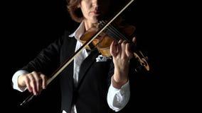 La muchacha arquea un violín en un cuarto oscuro Fondo negro Cierre para arriba almacen de video