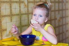 la muchacha arranca con los dientes un pedazo de pan que come la sopa Fotos de archivo libres de regalías