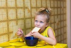 la muchacha arranca con los dientes un pedazo de pan que come la sopa Imagen de archivo