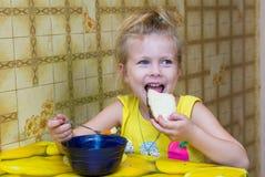la muchacha arranca con los dientes un pedazo de pan que come la sopa Imagenes de archivo