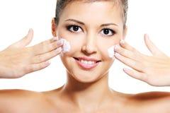 La muchacha asiática aplica la crema cosmética en cara Imágenes de archivo libres de regalías