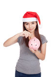 La muchacha asiática con el sombrero rojo de santa puso una moneda para picar la hucha Fotos de archivo