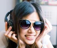 La muchacha asiática con las lentes es escucha la música Foto de archivo