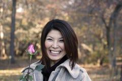 La muchacha asiática con se levantó Fotografía de archivo libre de regalías