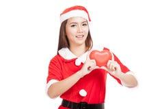 La muchacha asiática de la Navidad con Santa Claus viste con el corazón rojo Imagen de archivo