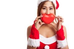 La muchacha asiática de la Navidad con Santa Claus viste con el corazón rojo Foto de archivo