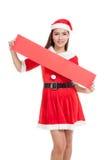 La muchacha asiática de la Navidad con Santa Claus viste con la muestra en blanco Fotografía de archivo