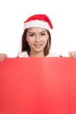 La muchacha asiática de la Navidad con Santa Claus viste con la muestra en blanco Imagen de archivo libre de regalías