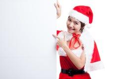 La muchacha asiática de la Navidad con Santa Claus viste el punto para esconder el si Imagenes de archivo