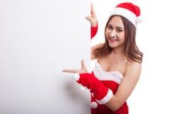 La muchacha asiática de la Navidad con Santa Claus viste el punto para esconder el si Imágenes de archivo libres de regalías