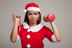 La muchacha asiática de la Navidad con Santa Claus viste, la cinta métrica a Imagenes de archivo