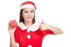La muchacha asiática de la Navidad manosea con los dedos para arriba con la ropa y el rojo de Santa Claus Imágenes de archivo libres de regalías