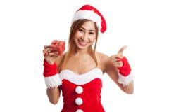 La muchacha asiática de la Navidad manosea con los dedos para arriba con la ropa y el rojo de Santa Claus Foto de archivo libre de regalías