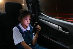 La muchacha asiática de los estudiantes goza de un teléfono en los coches personales mientras que CCB Imagenes de archivo