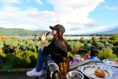 La muchacha asiática del adolescente goza y sosteniendo la botella de cerveza Imágenes de archivo libres de regalías