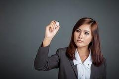 La muchacha asiática del negocio escribe en el aire Imagen de archivo libre de regalías