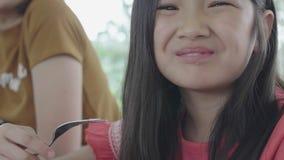 La muchacha asiática del niño está comiendo el desayuno por la bifurcación almacen de metraje de vídeo