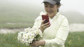 La muchacha asiática disfruta las flores rasgadas en un claro en la niebla metrajes