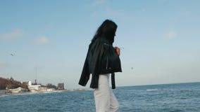 La muchacha asiática en una chaqueta de cuero va contra el mar almacen de metraje de vídeo
