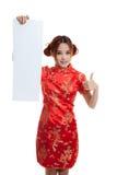 La muchacha asiática en vestido chino del cheongsam manosea con los dedos para arriba con el espacio en blanco rojo Foto de archivo