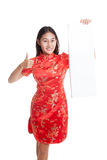 La muchacha asiática en vestido chino del cheongsam manosea con los dedos para arriba con el espacio en blanco rojo Imagen de archivo libre de regalías