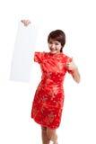 La muchacha asiática en vestido chino del cheongsam manosea con los dedos para arriba con el espacio en blanco rojo Imagenes de archivo