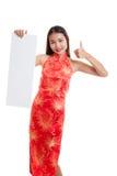 La muchacha asiática en vestido chino del cheongsam manosea con los dedos para arriba con el espacio en blanco rojo Fotografía de archivo
