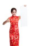 La muchacha asiática en vestido chino del cheongsam manosea con los dedos para arriba con el espacio en blanco rojo Fotos de archivo libres de regalías