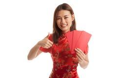 La muchacha asiática en vestido chino del cheongsam manosea con los dedos para arriba con rojo envuelve Imagenes de archivo