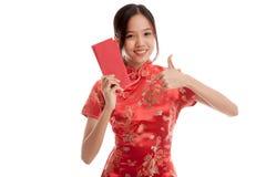 La muchacha asiática en vestido chino del cheongsam manosea con los dedos para arriba con rojo envuelve Imagen de archivo