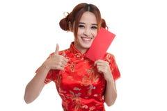La muchacha asiática en vestido chino del cheongsam manosea con los dedos para arriba con rojo envuelve Fotos de archivo