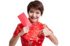 La muchacha asiática en vestido chino del cheongsam manosea con los dedos para arriba con rojo envuelve Foto de archivo libre de regalías
